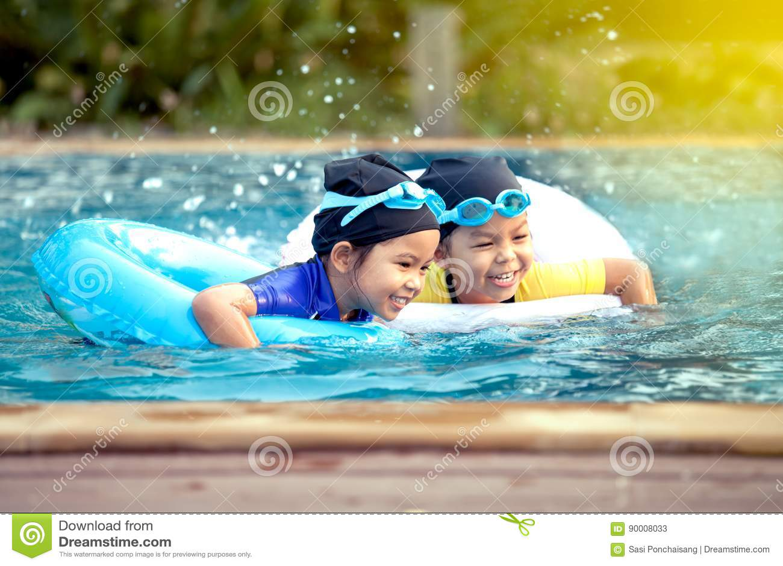 Dwa azjatykciej małej dziewczynki ma zabawę pływać w pływackim basenie