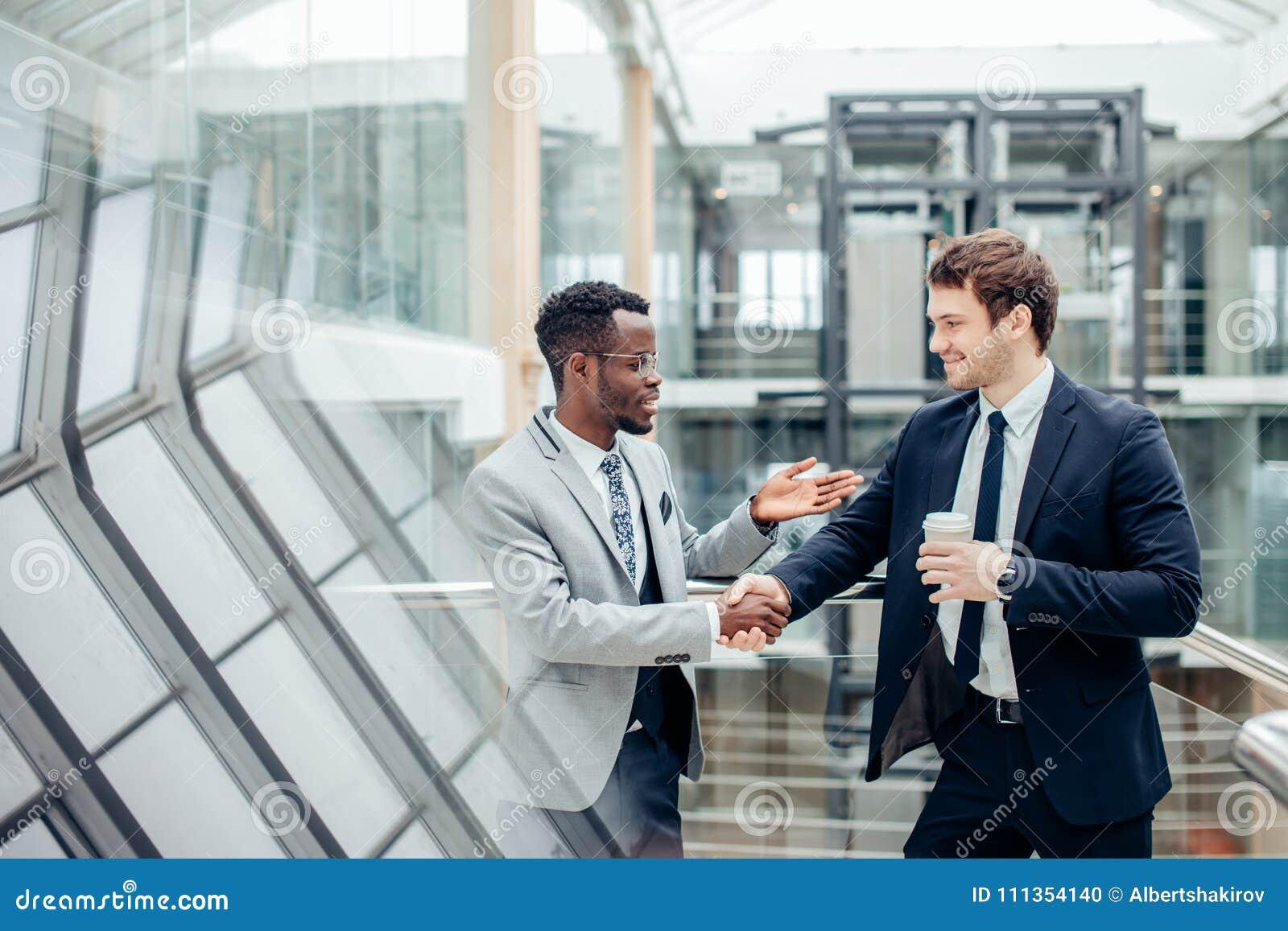 Dwa biznesmenów multiracial handshaking w nowożytnym biurze dla końcówki wielka transakcja