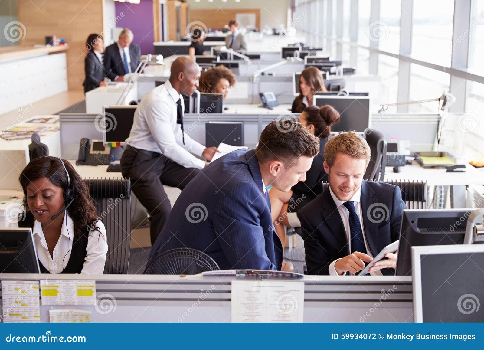 Dwa biznesmena dyskutuje pracę w ruchliwie, otwartym planu biurze,