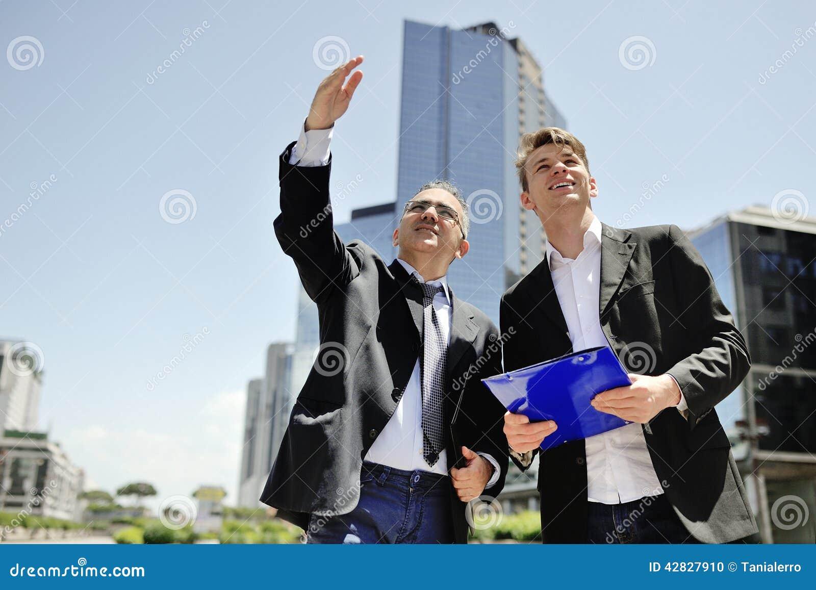 Dwa biznesmena pracuje o nowym projekcie na tło budynkach biurowych