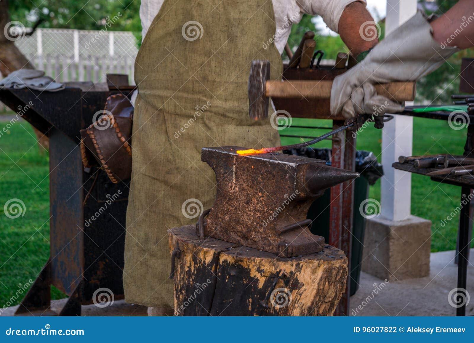 Dwa blacksmiths blisko kowadła Jeden sieka podkowę z baleronem