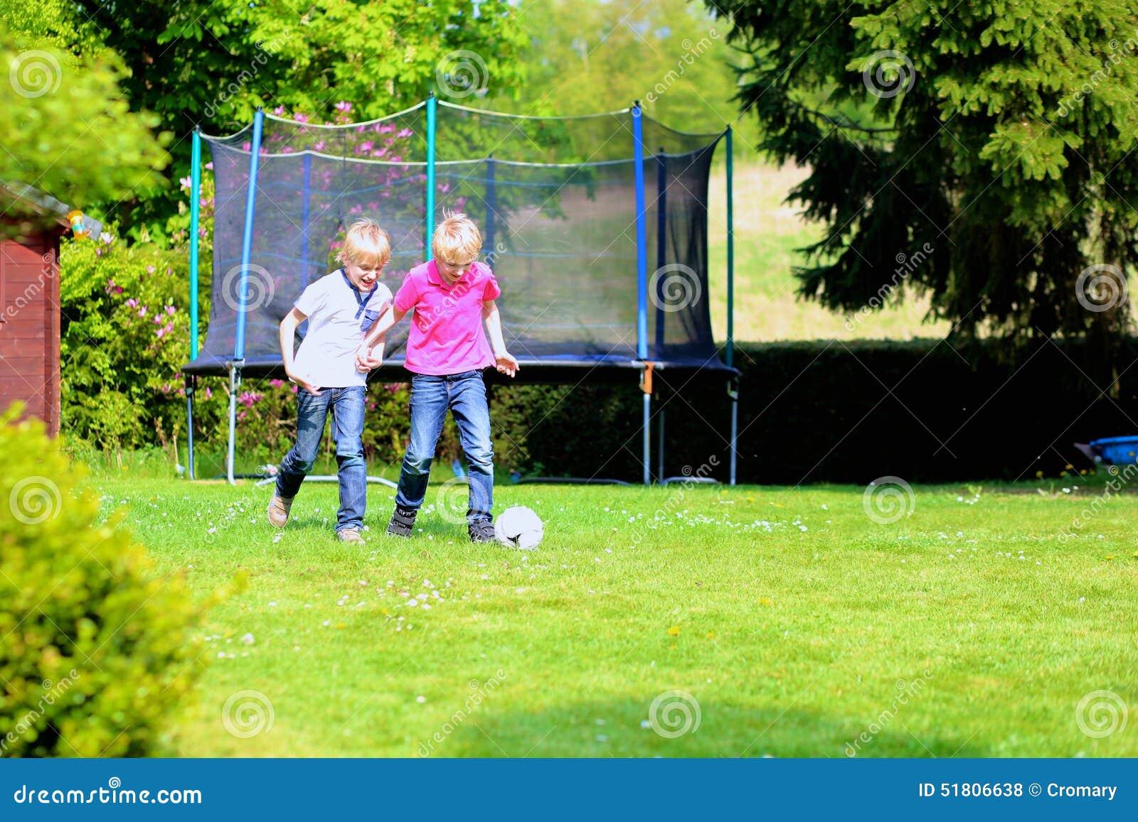 Dwa brata bawić się piłkę nożną w ogródzie