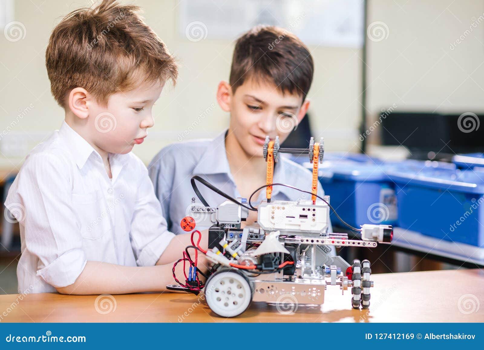 Dwa brata dzieciaka bawić się z robot zabawką przy szkolną robotyki klasą, salową