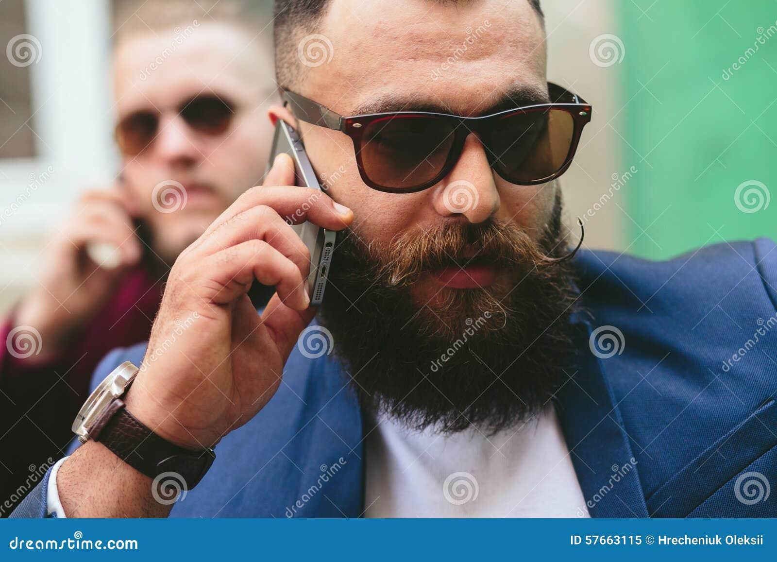 Dwa brodaty biznesmen patrzeje telefon
