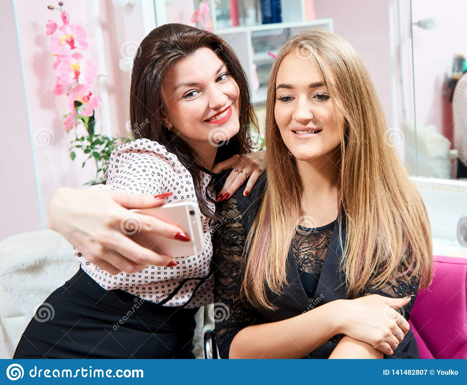 Dwa brunetki dziewczyny i blondynka robią selfie w piękno salonie
