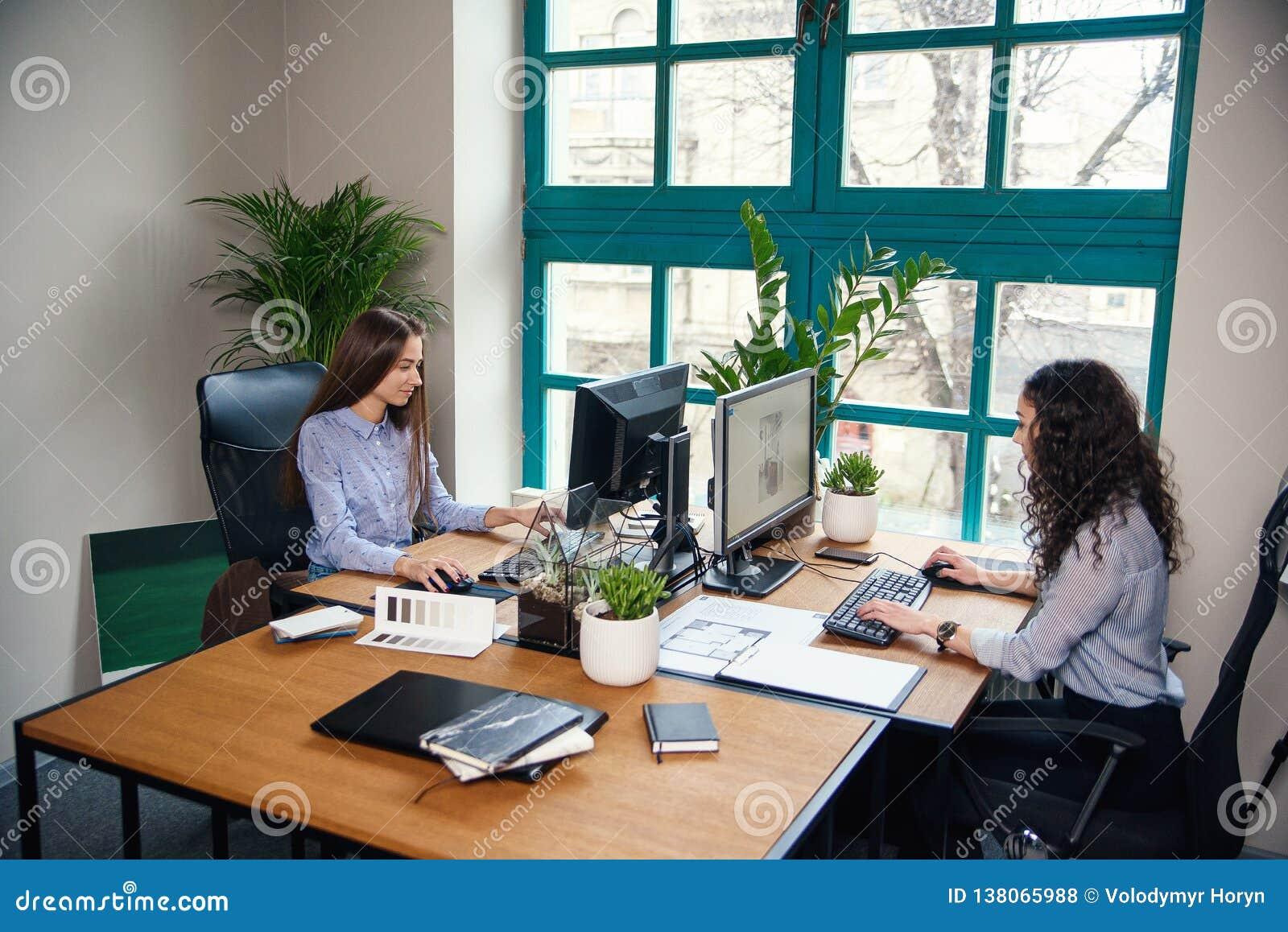 Dwa caucasian biznesowej kobiety pisać na maszynie na komputerze podczas pracować w nowożytnym architekta biurze