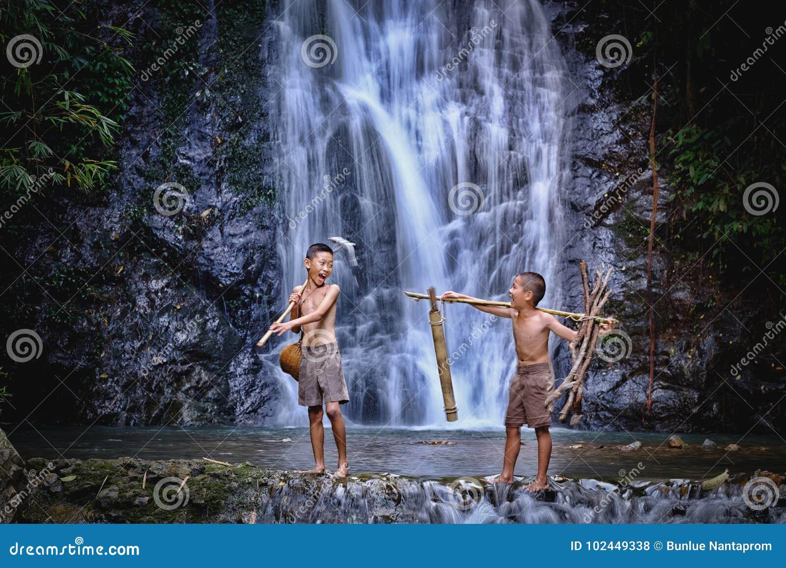 Dwa chłopiec śmiechu połów przy siklawy wsią Thailand Fishin