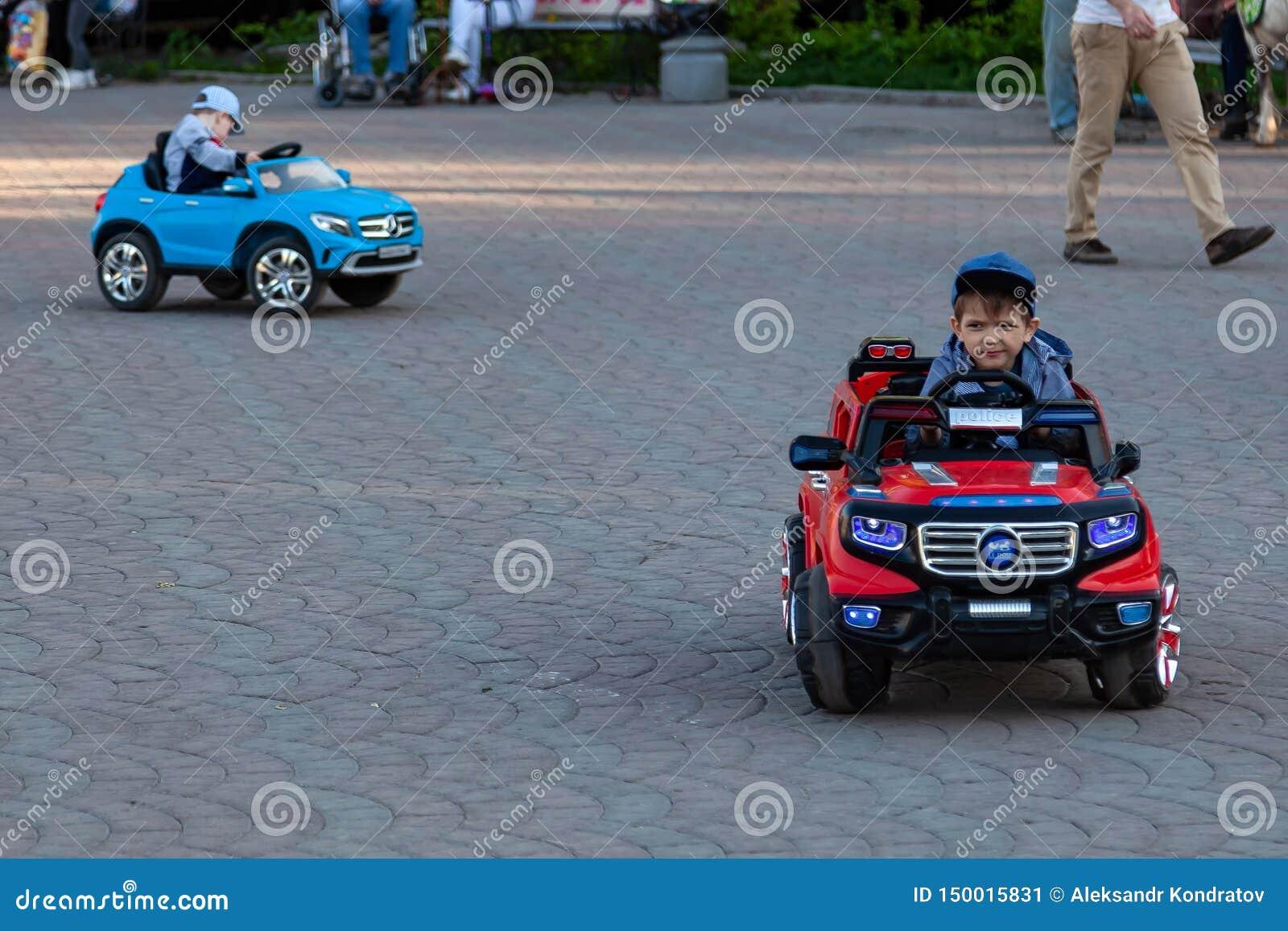 Dwa chłopiec jadą na czerwonych i błękitnych elektrycznych samochodach podczas gdy chodzący z ich rodzicami w miasto parku z ziel