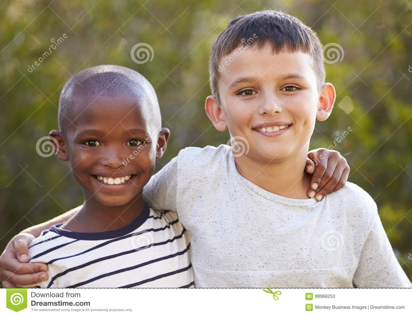 Dwa chłopiec, ręki wokoło each inny ono uśmiecha się kamera outdoors