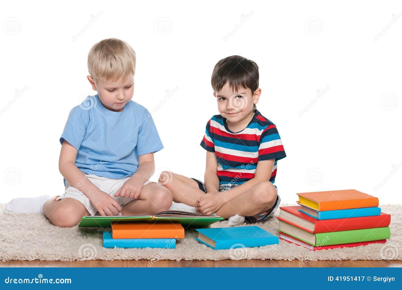 Dwa chłopiec z książkami na podłoga