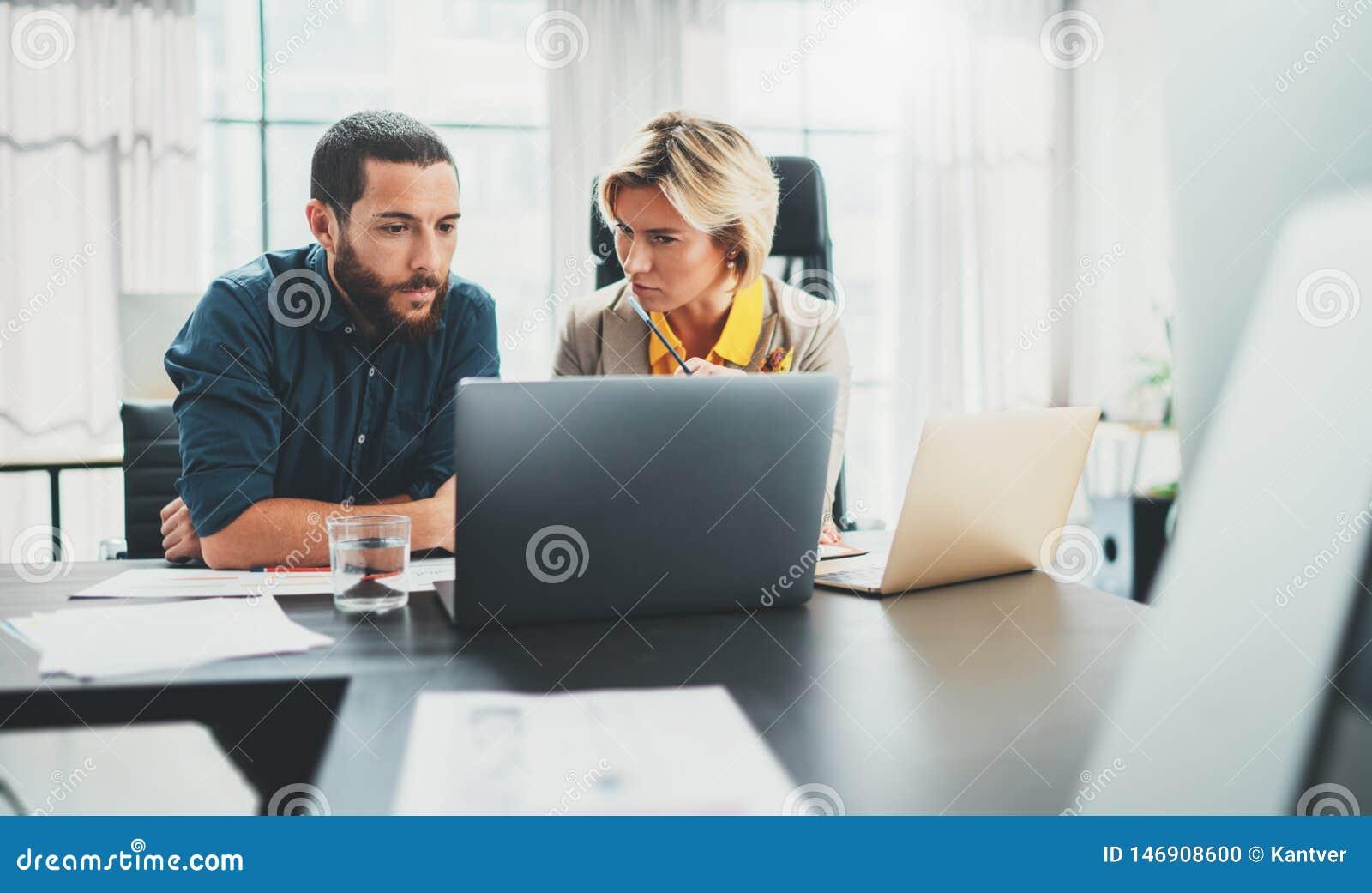 Dwa coworkers przy pracowa? proces M?oda kobieta pracuje wraz z koleg? przy nowo?ytnym biurem Pracy zespo?owej poj?cie