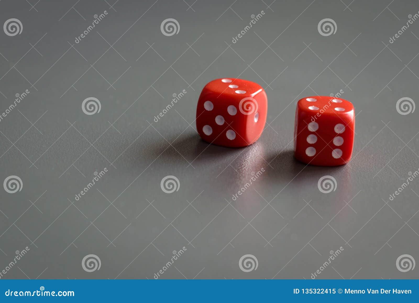 Dwa czerwonej kostki do gry odizolowywającej na popielatym tle