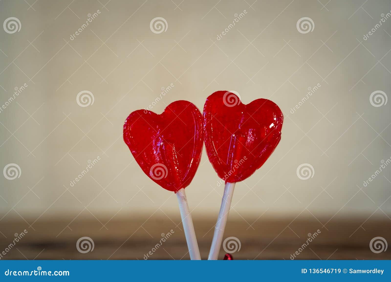 Dwa czerwony serce kształtował lizaki jako metafora miłość, więź i walentynka dzień, pojęcie