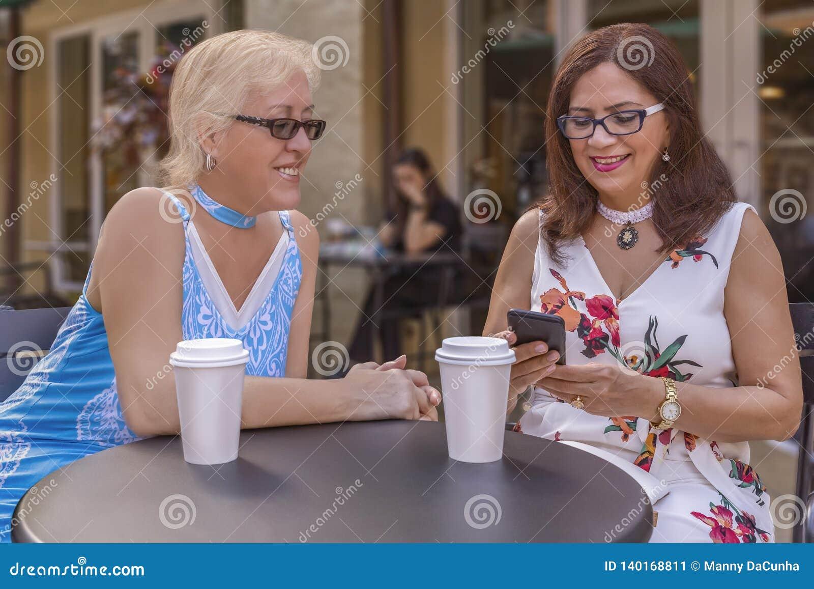 Dwa dojrzałego przyjaciela cieszą się kawę outdoors podczas gdy patrzejący smartphone