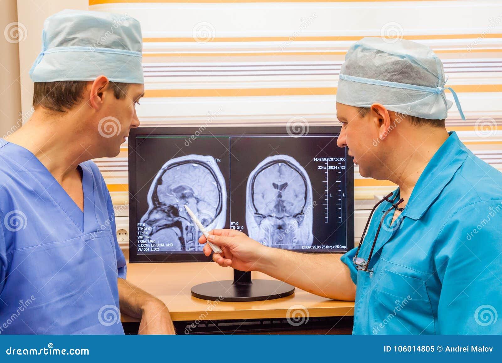 Dwa Dojrzałej lekarki Egzamininuje MRI obraz cyfrowego mózg