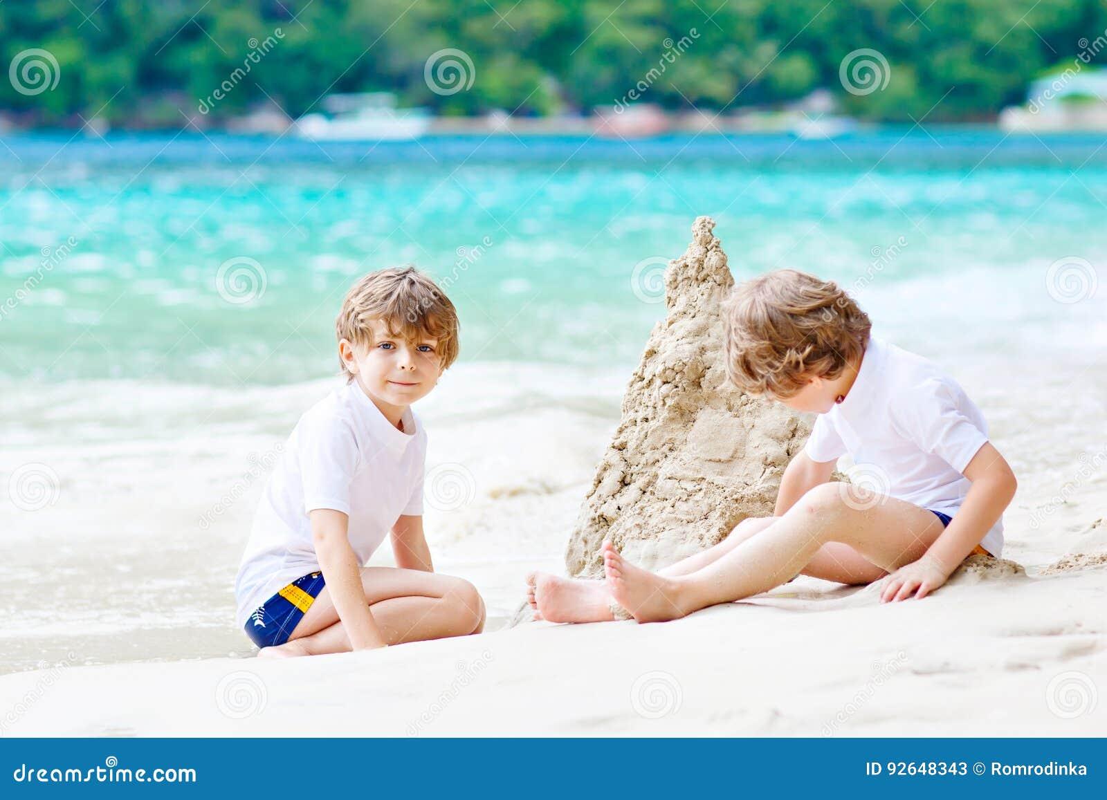 Dwa dzieciak chłopiec buduje piasek roszują na tropikalnej plaży