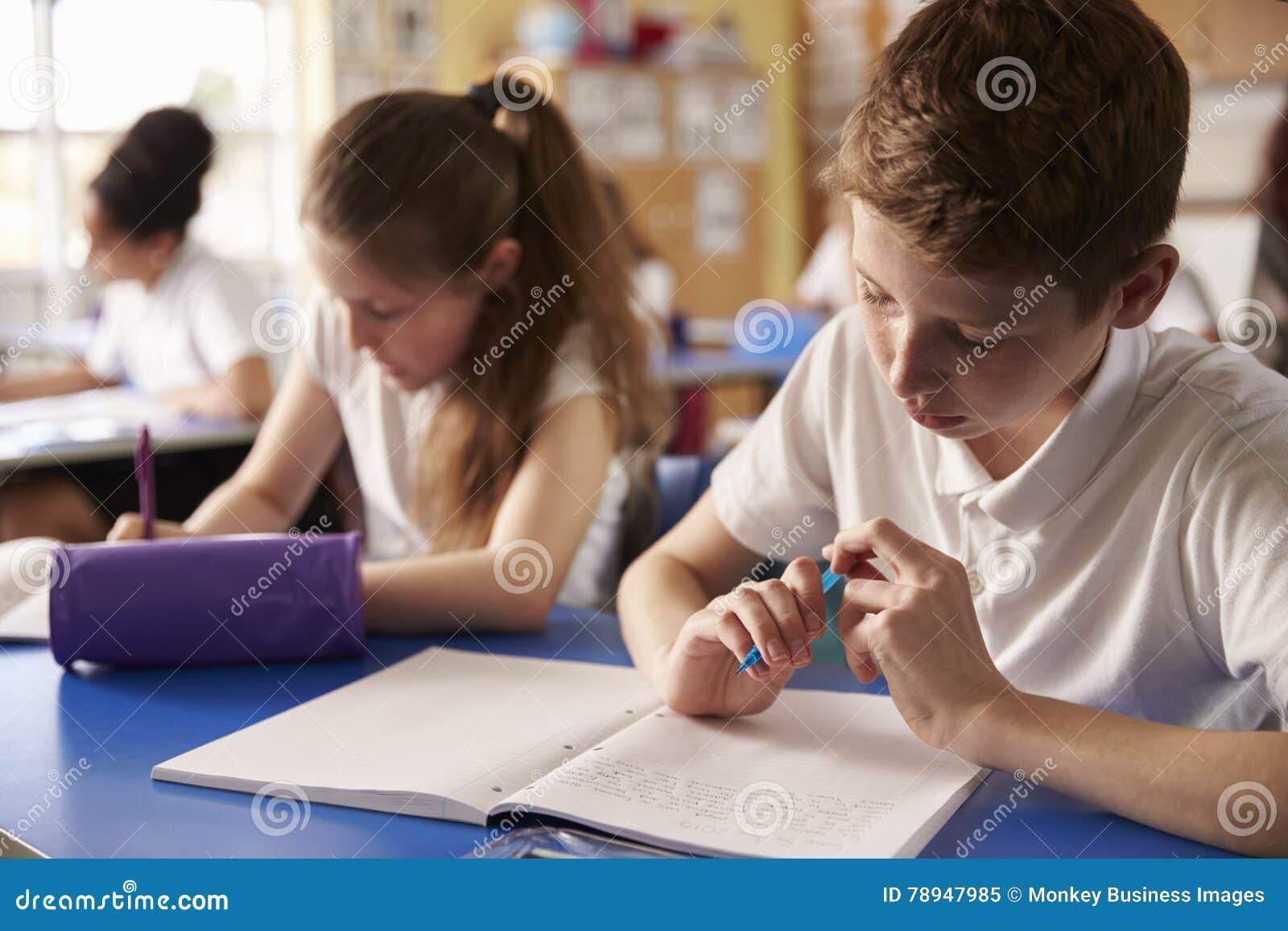 Dwa dzieciaka pracuje przy ich biurkami w szkole podstawowej, zamykają up