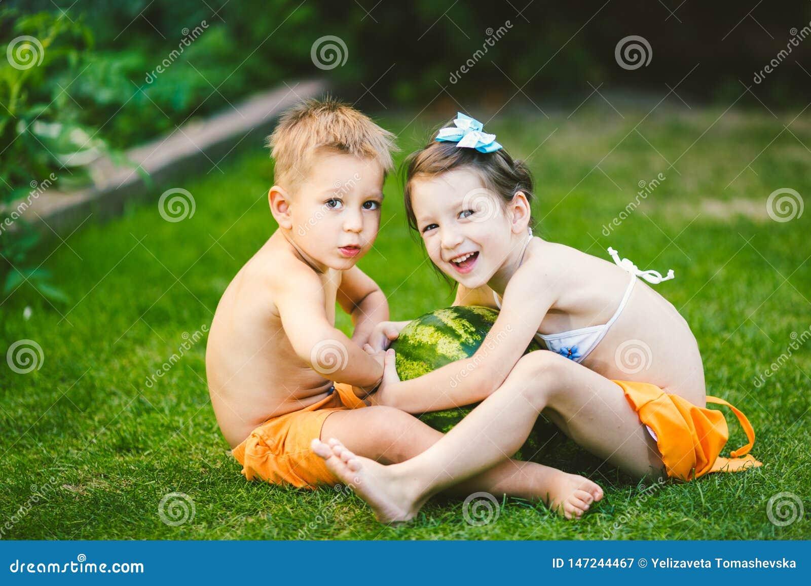 Dwa dziecka Kaukaski brat i siostra, siedzi na zielonej trawie w podw?rko dom i ?ciska du?ego smakowitego s?odkiego arbuza,
