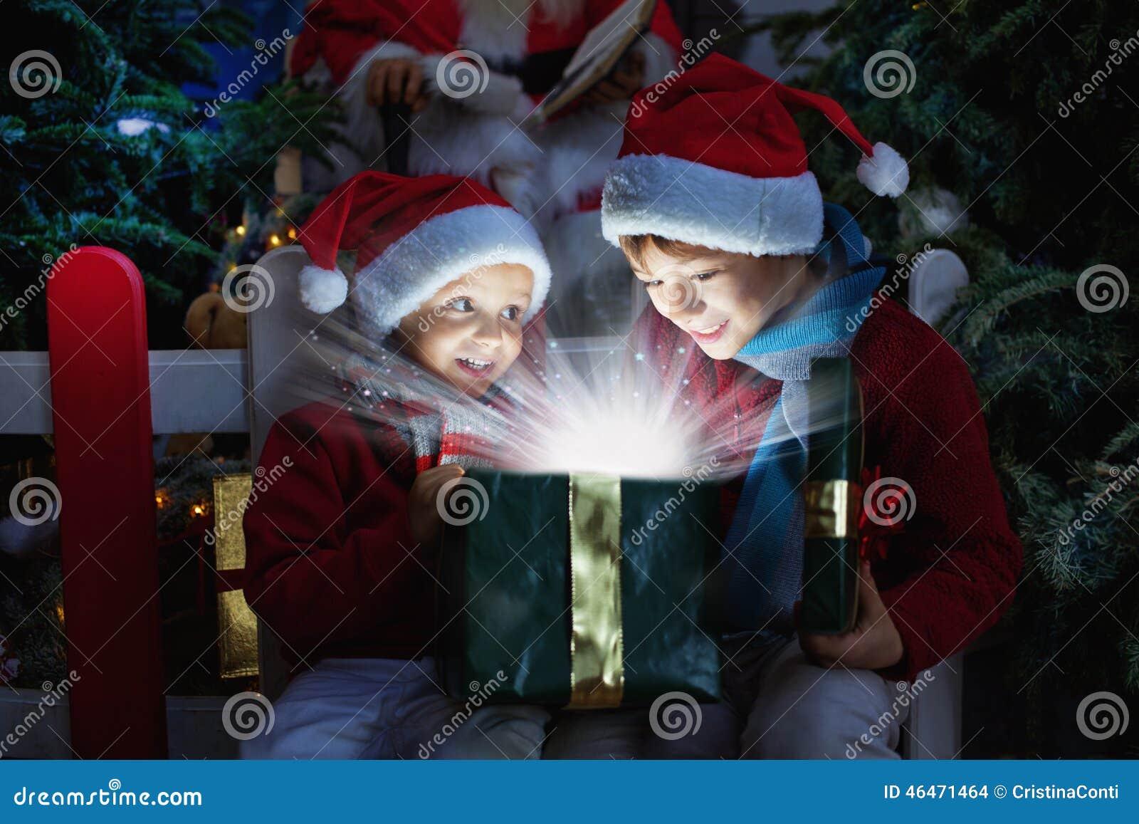 Dwa dziecka otwiera Bożenarodzeniowego prezent