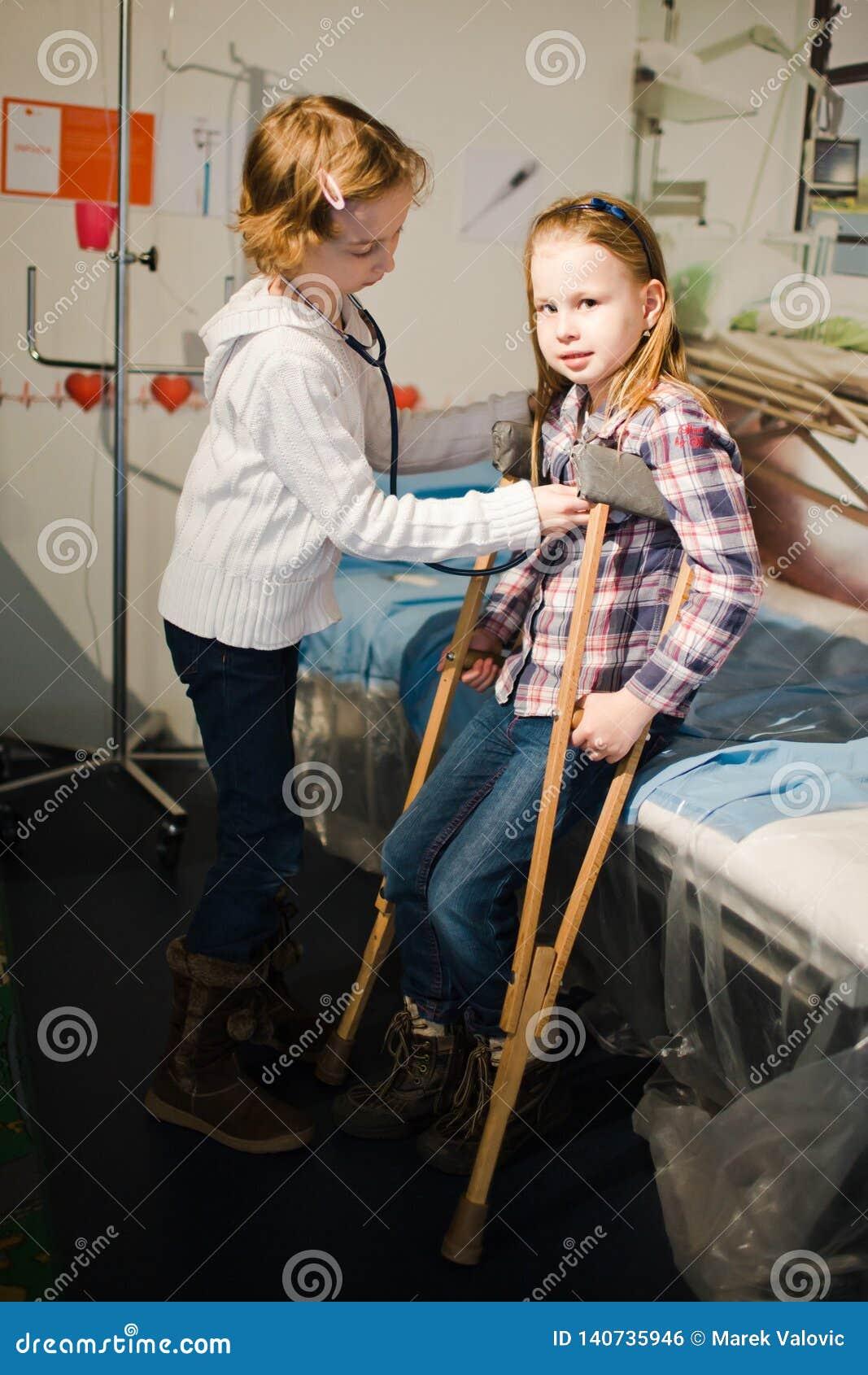 Dwa dziecko udaje być doktorski i cierpliwy - stetoskop i sprzęgła
