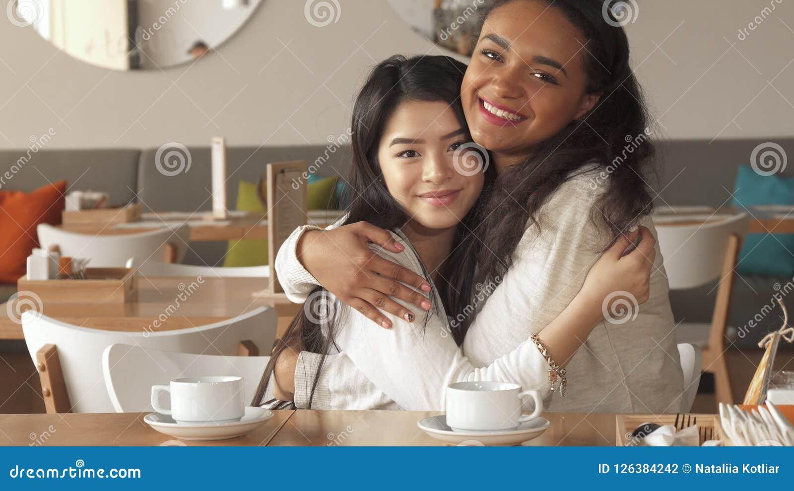 Dwa dziewczyn uściśnięcie przy kawiarnią