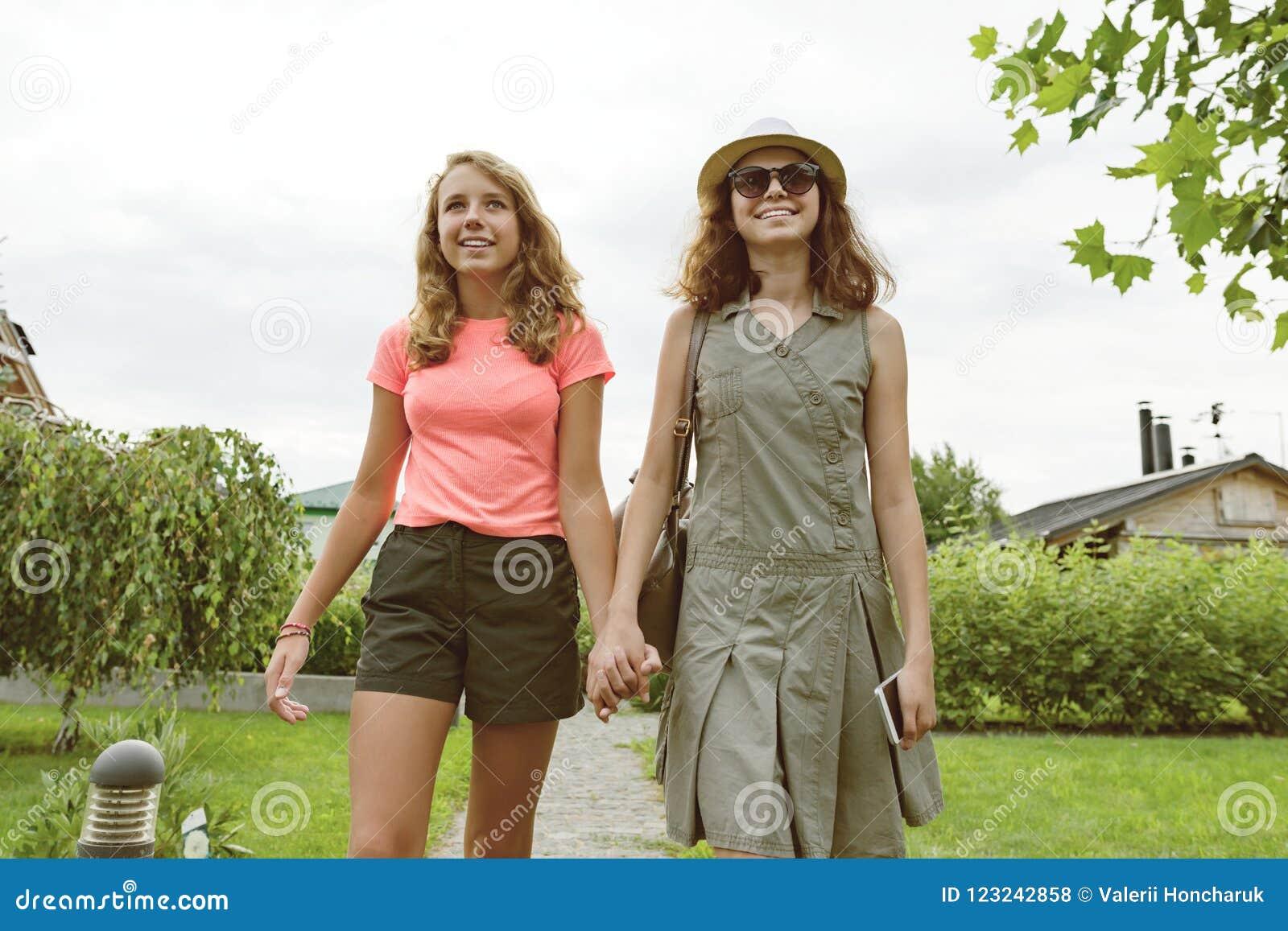 Dwa dziewczyna przyjaciela iść trzymać ręki, tło gazonu ścieżka blisko domu