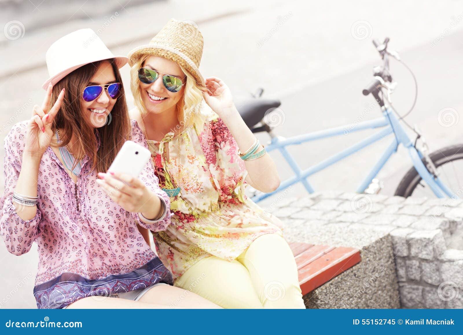 Dwa dziewczyna przyjaciela używa smartphone podczas gdy jadący tandemowego bicykl