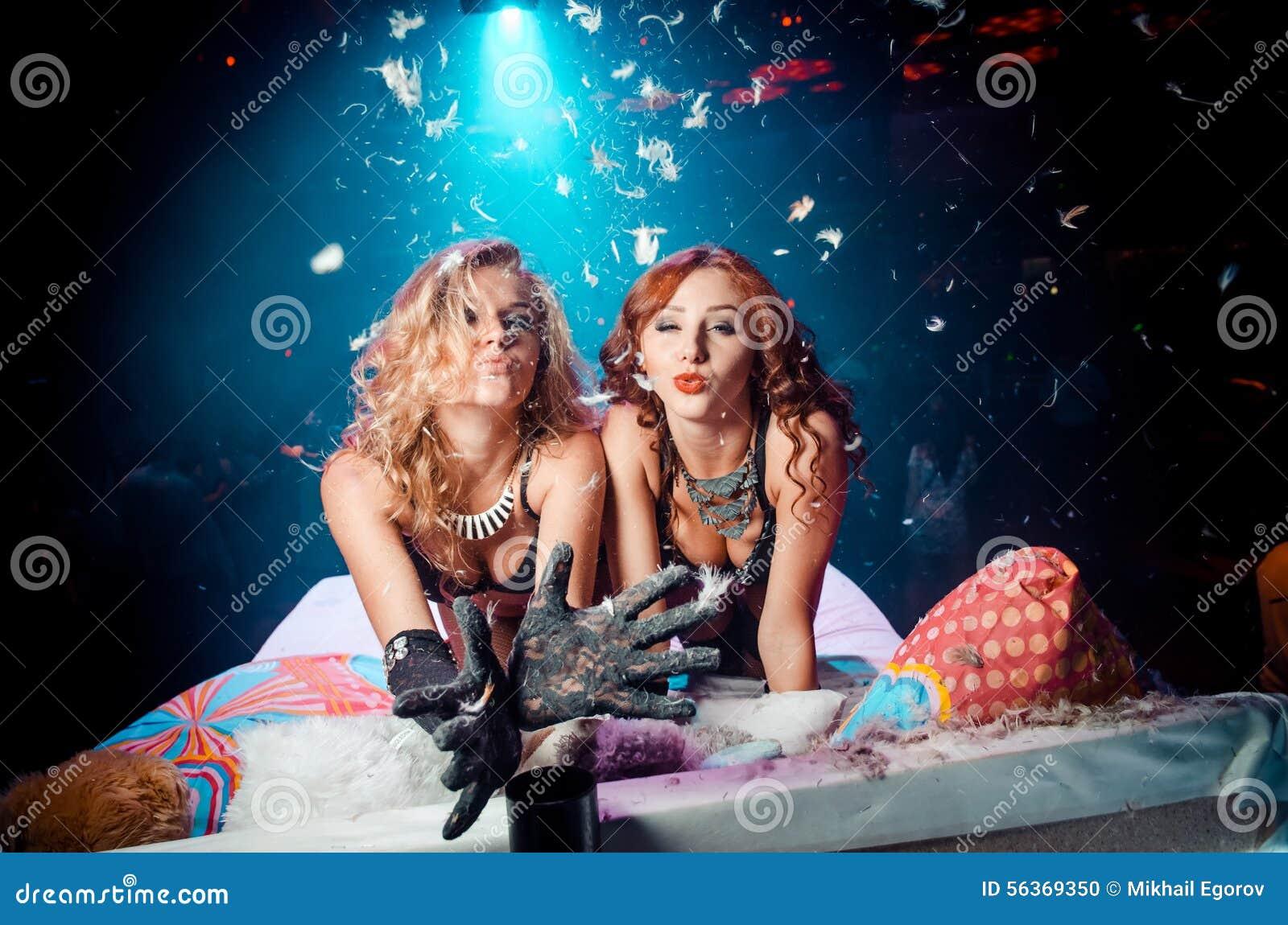 Dwa dziewczyny na łóżkowym dosłania powietrza buziaku