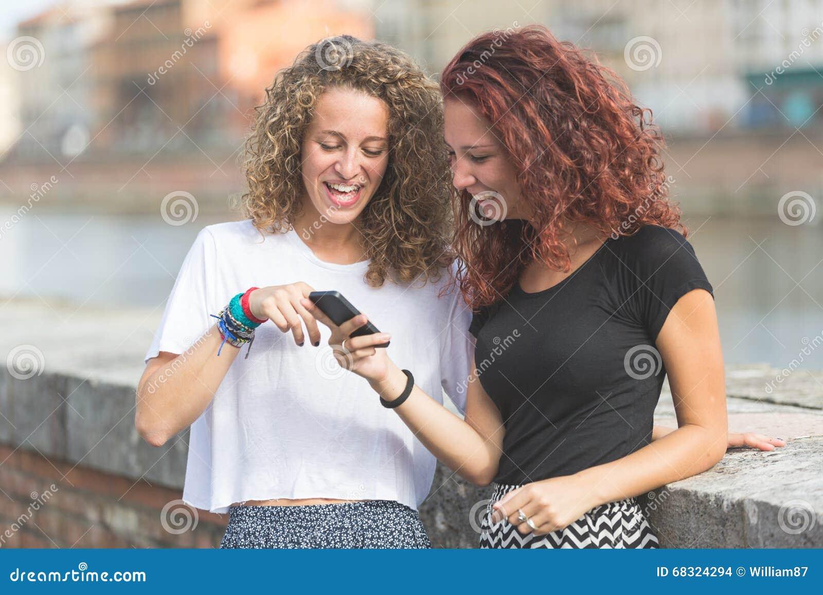 Dwa dziewczyny patrzeje mądrze telefon w mieście