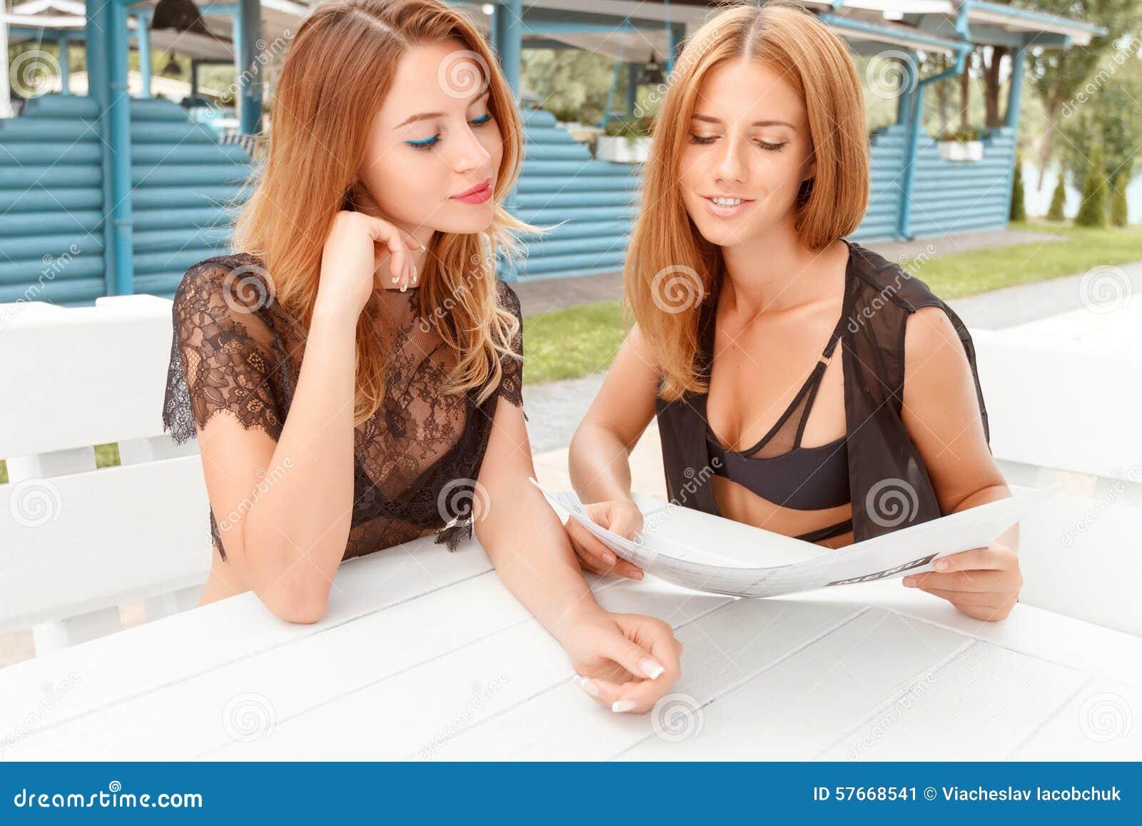 Dwa dziewczyny patrzeje przez ceny listy
