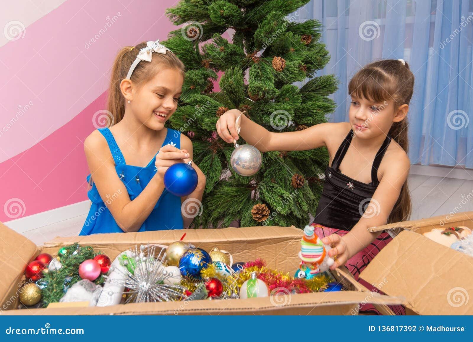 Dwa dziewczyny są biorąc pod uwagę piłki w pudełku z nowy rok zabawkami
