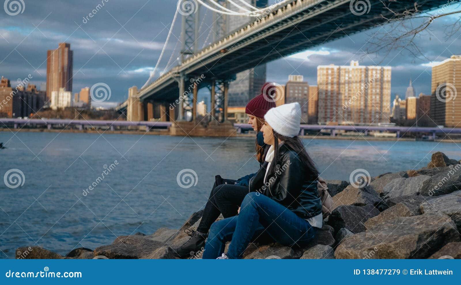 Dwa dziewczyny siedzą przy Manhattan mostem i cieszą się ich zwiedzającą wycieczkę Nowy Jork