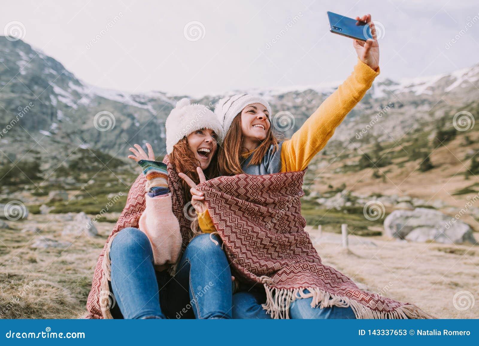 Dwa dziewczyny siedzą w łące i biorą obrazek z ich wiszącą ozdobą