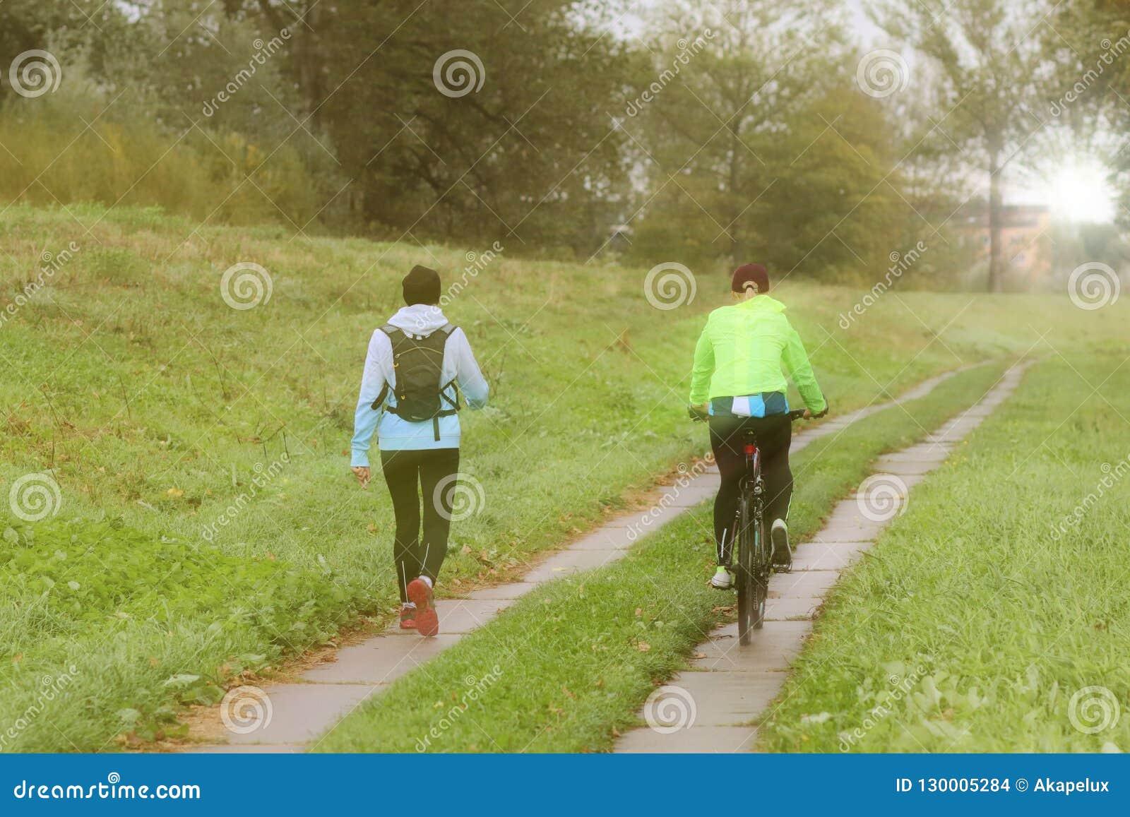 Dwa dziewczyny sztuki sporta w pogodnej ranek pogodzie Kolarstwo i odprowadzenie pod deszcz kroplami w pogodnej pogodzie Sport i