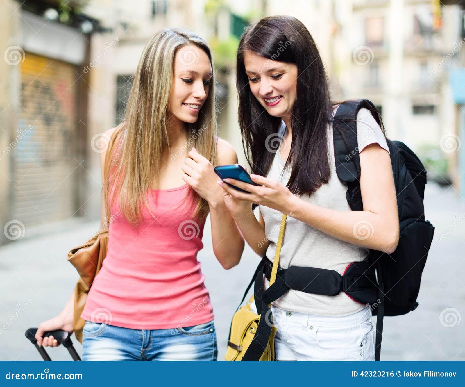 Dwa dziewczyny używa smartphone żegluje system