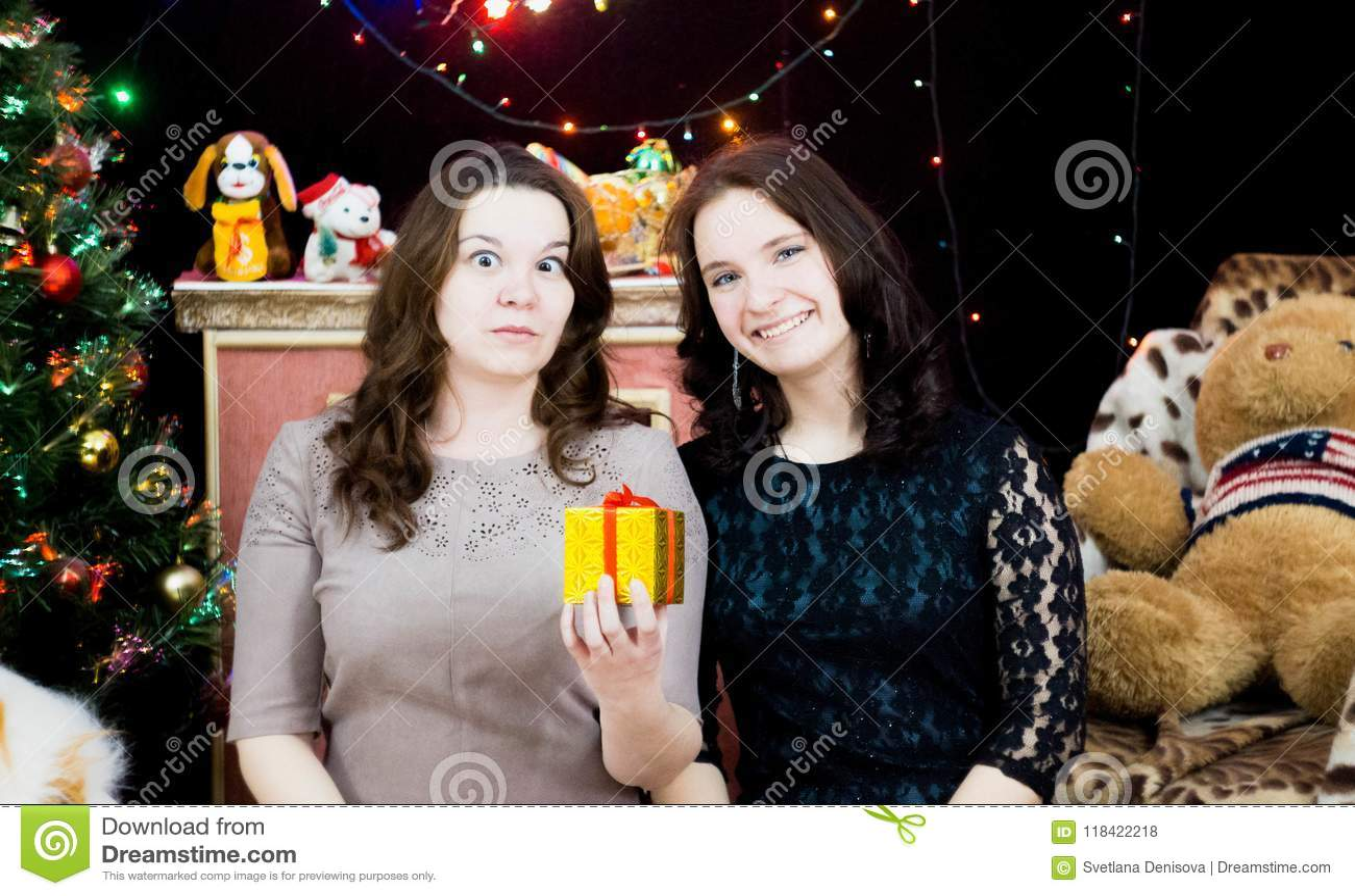 Dwa dziewczyny w Bożenarodzeniowym położeniu z prezentem w ich rękach