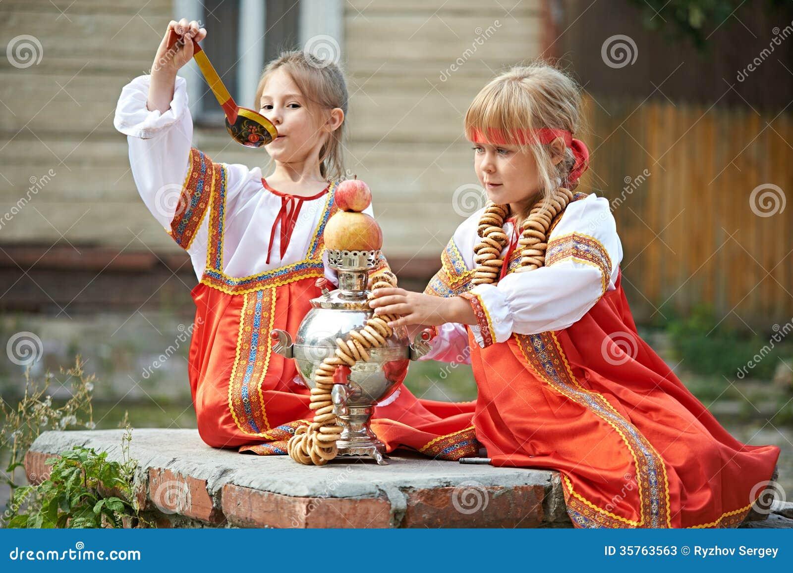 Dwa dziewczyny w Rosyjskich krajowych kostiumach z samowarem