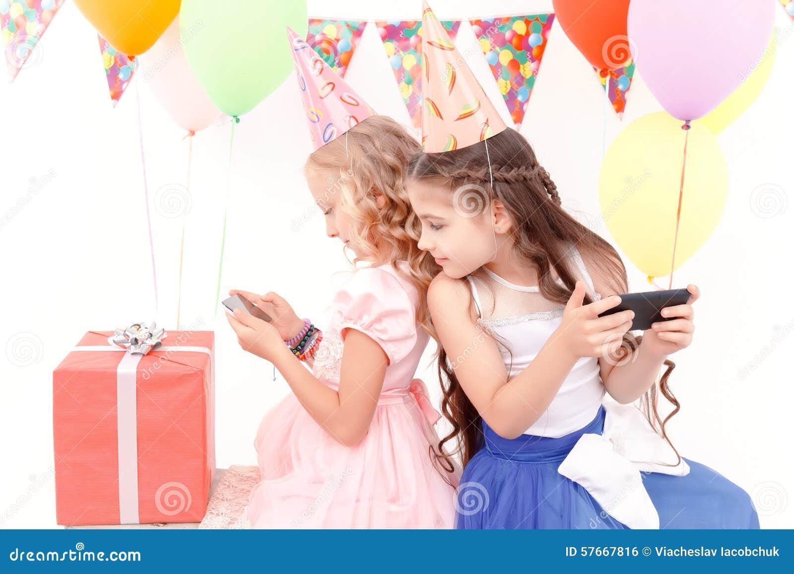 Dwa dziewczyny z telefonem komórkowym podczas przyjęcia urodzinowego