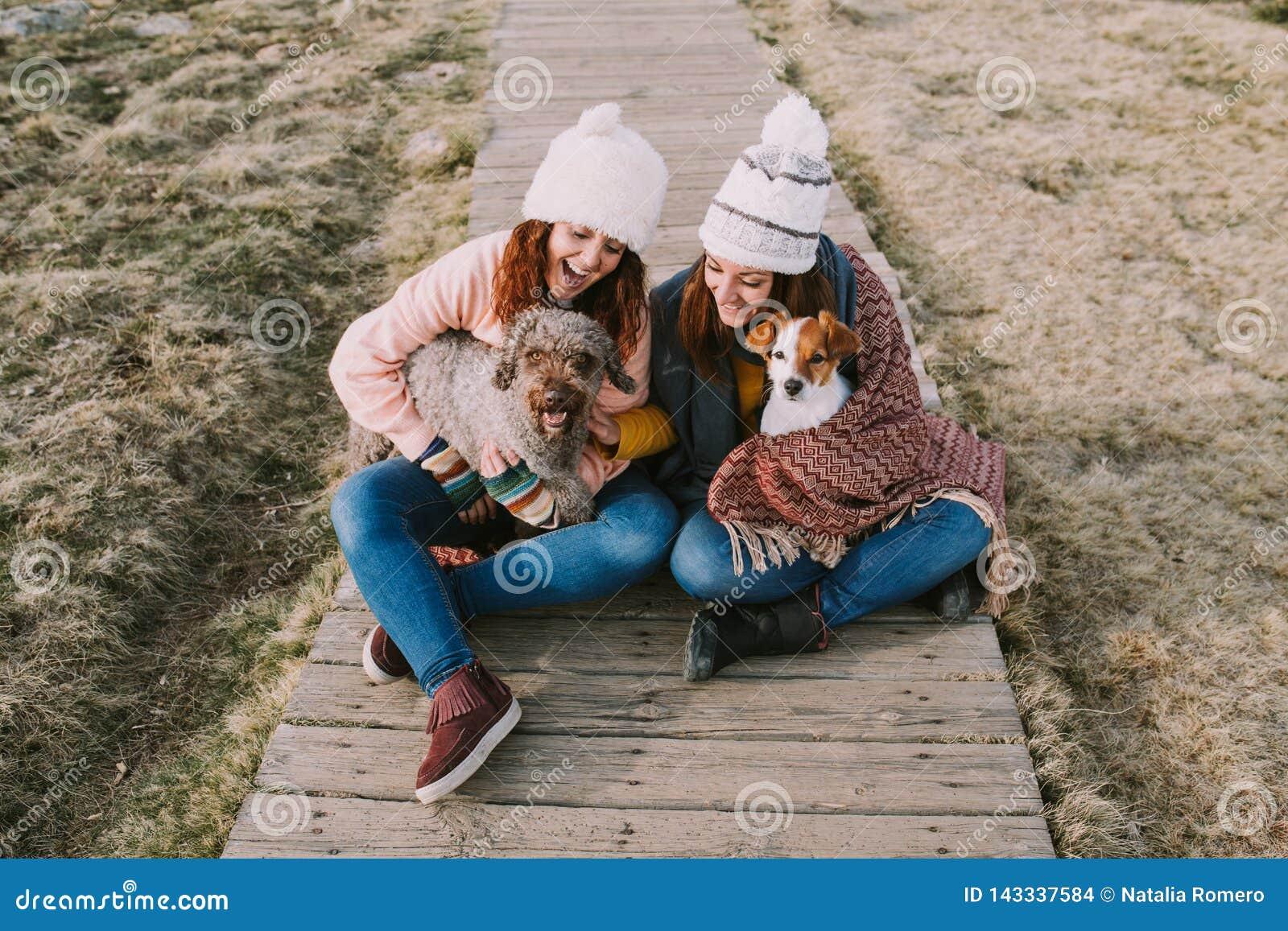 Dwa dziewczyny zawijają w koc podczas gdy bawić się z ich psami w łące