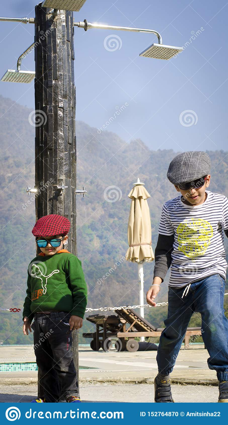 Dwa eleganckiego dzieciaka jest ubranym nakrętki ma zabawę wpólnie