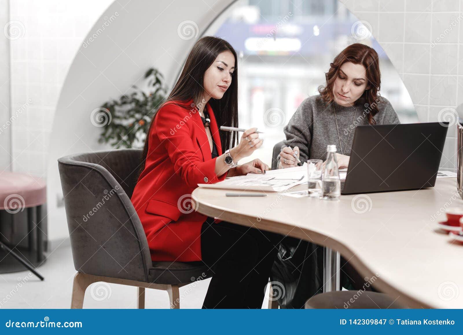 Dwa eleganckiego dziewczyny projektant wnętrz pracuje w biurze przy projekta projektem