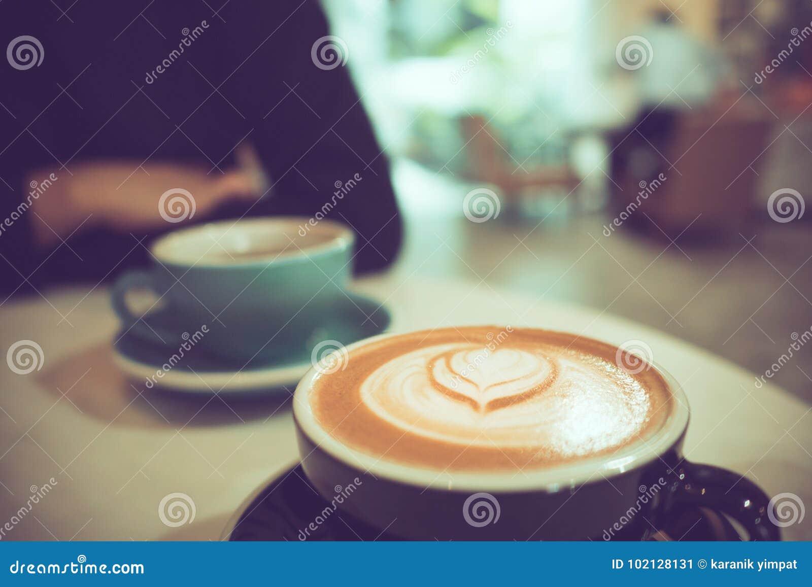 Dwa filiżanki gorąca kawa przy kawiarnią, jeden z kierową kształta latte sztuką