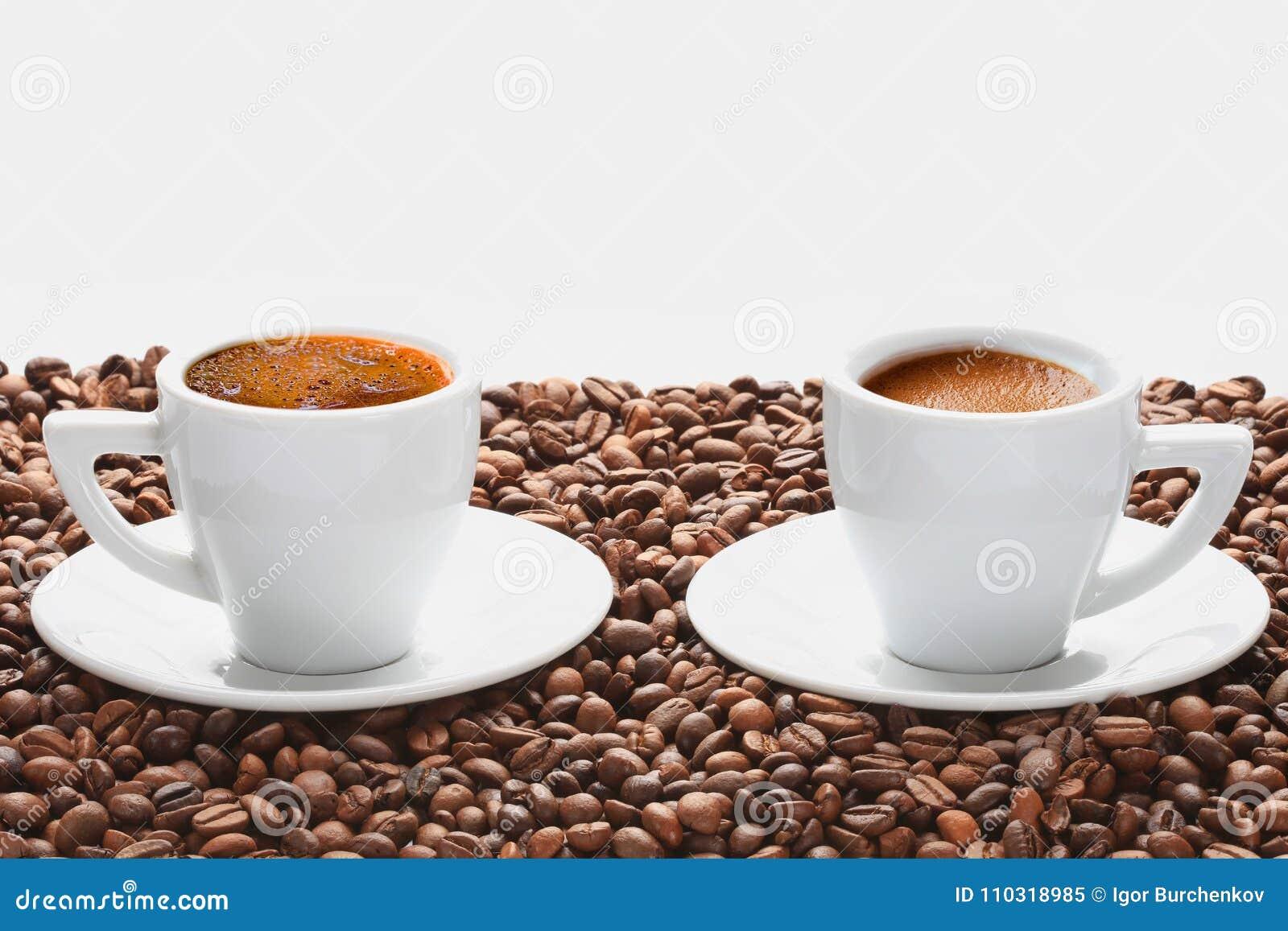 Dwa filiżanki gorąca kawa z kawowymi fasolami na białym tle