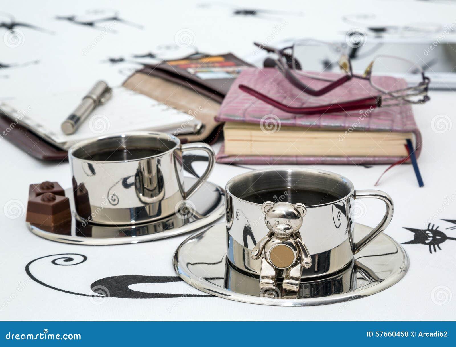 Dwa filiżanki kawy, szkła, notatnik w łóżku