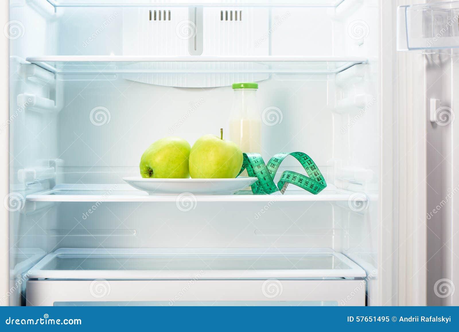 Dwa jabłka z pomiarową taśmą i szklaną butelką w chłodziarce