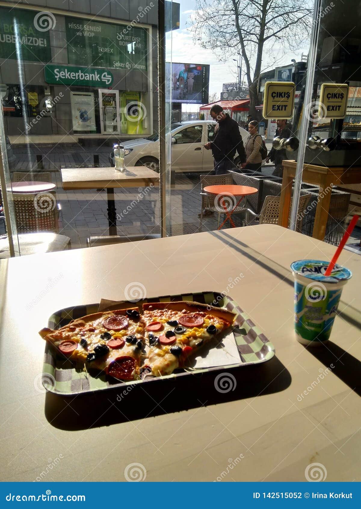 Dwa kawałka pizza pn talerz z ulicznym widokiem