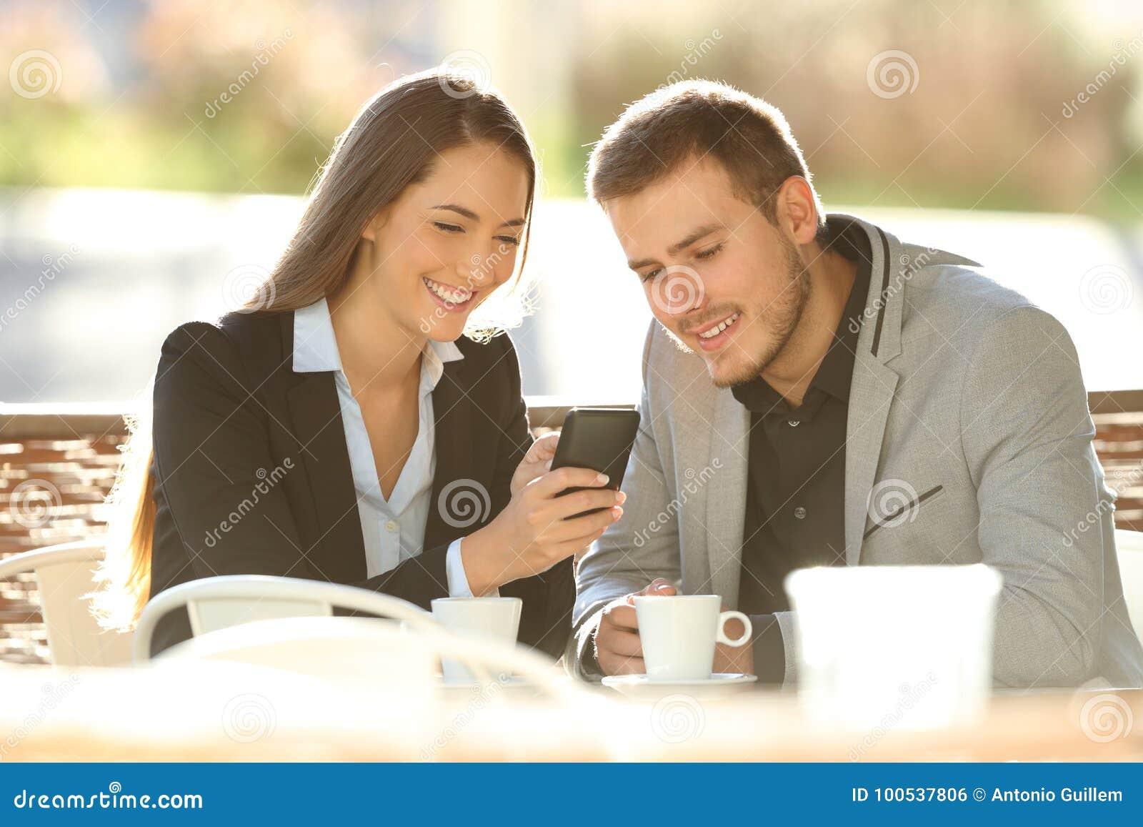 Dwa kierownictwa używa mądrze telefon w sklep z kawą