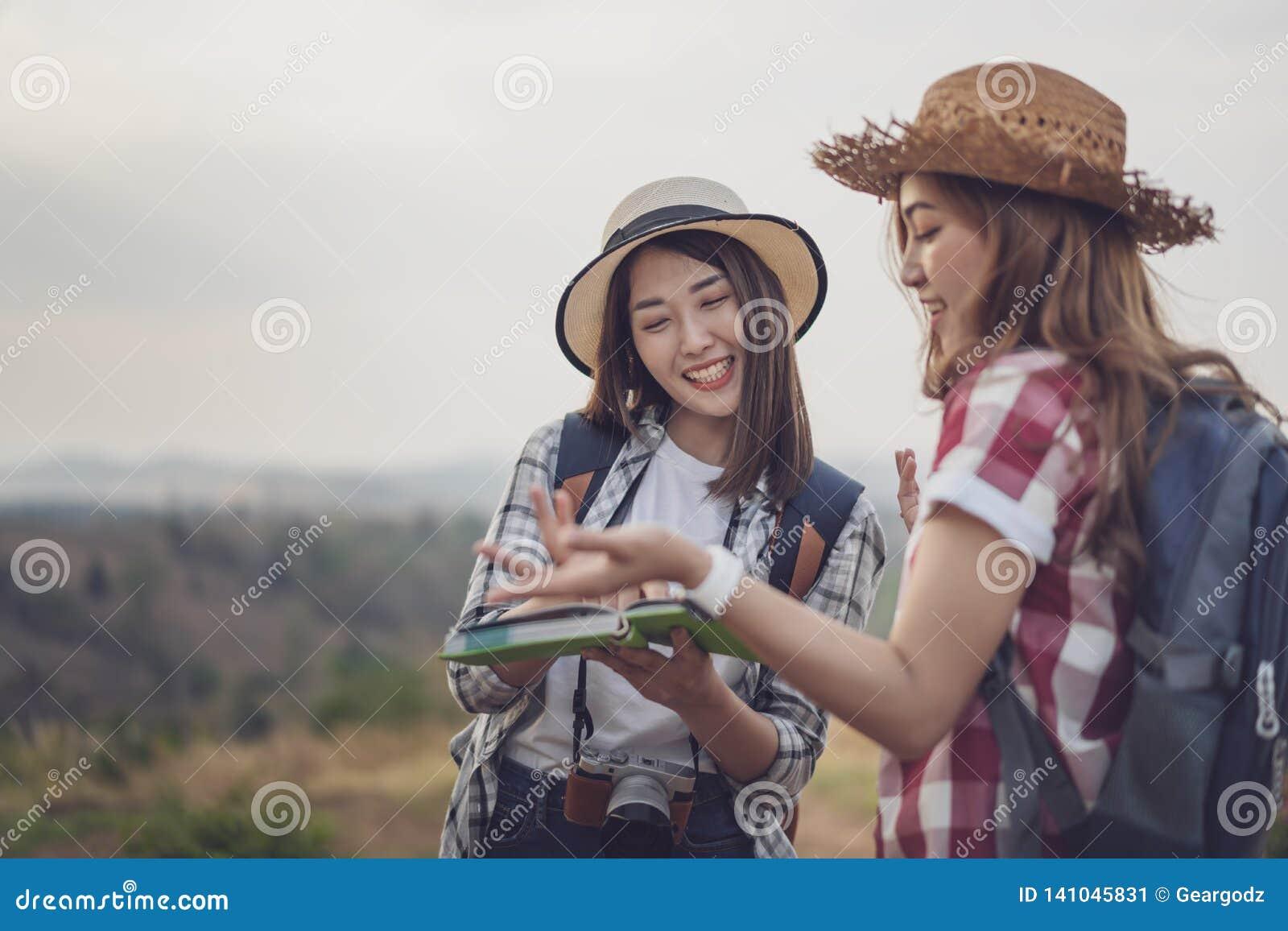 Dwa kobiet gmerania kierunek na lokacji mapie podczas gdy podróżujący