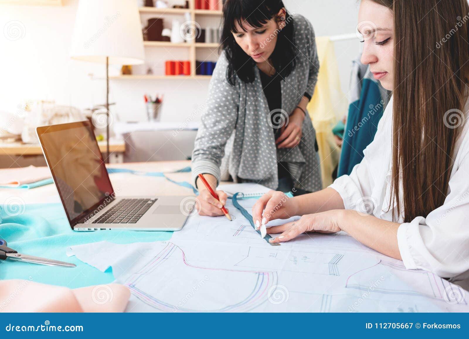 Dwa kobiet krawcowa robi projektant odzieży w sala wystawowej Młoda żeńska fachowa szwaczka pracuje przy szyć