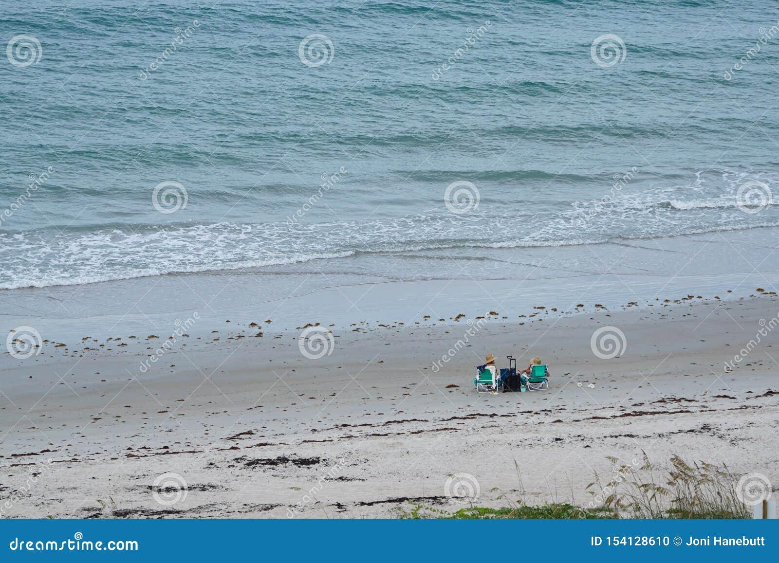 Dwa kobieta przyjaciela ma koktajle na plaży